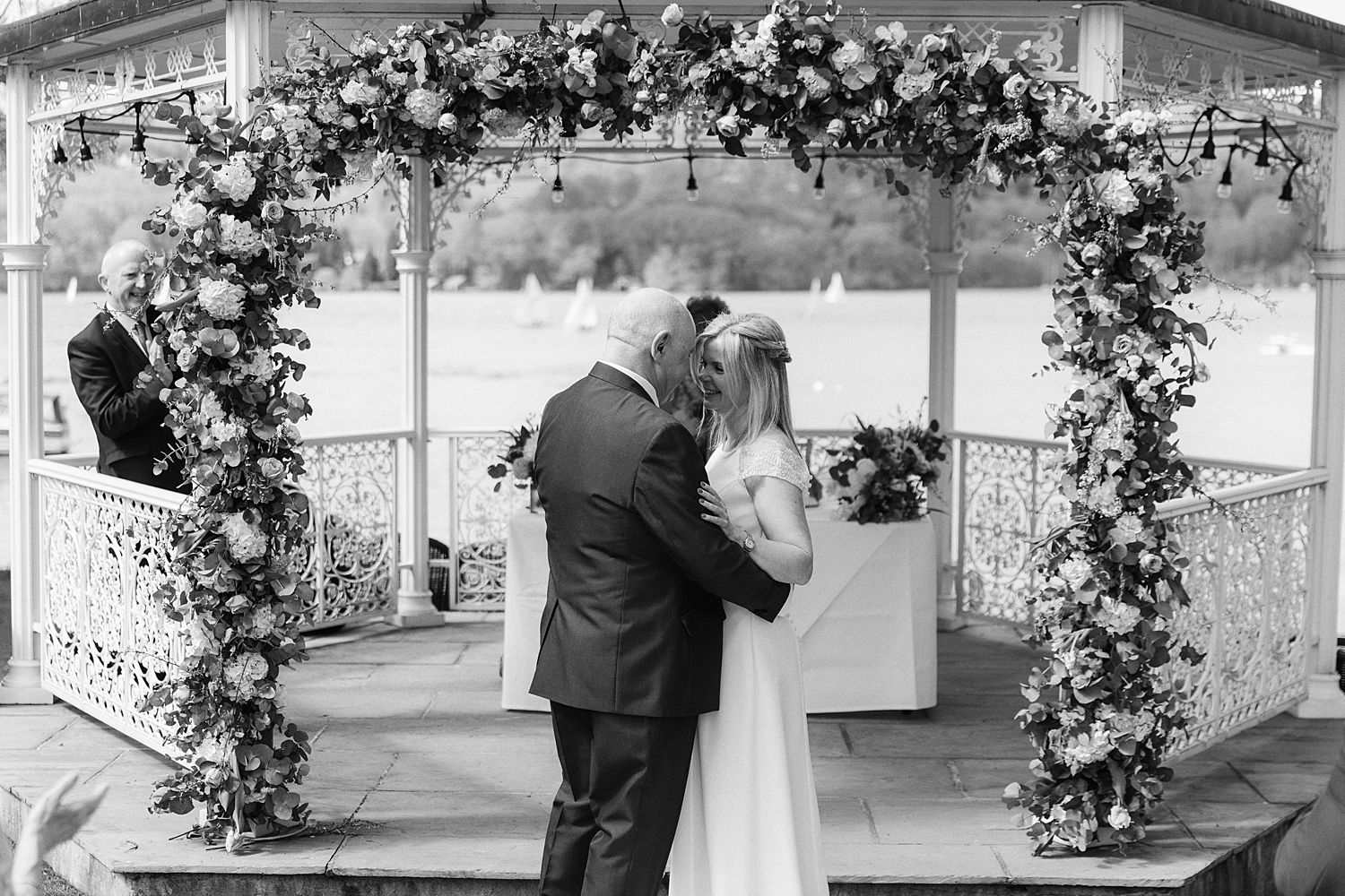 Bride and groom embrace at outdoor wedding ceremony at Storrs Hall, Bowness on Windermere