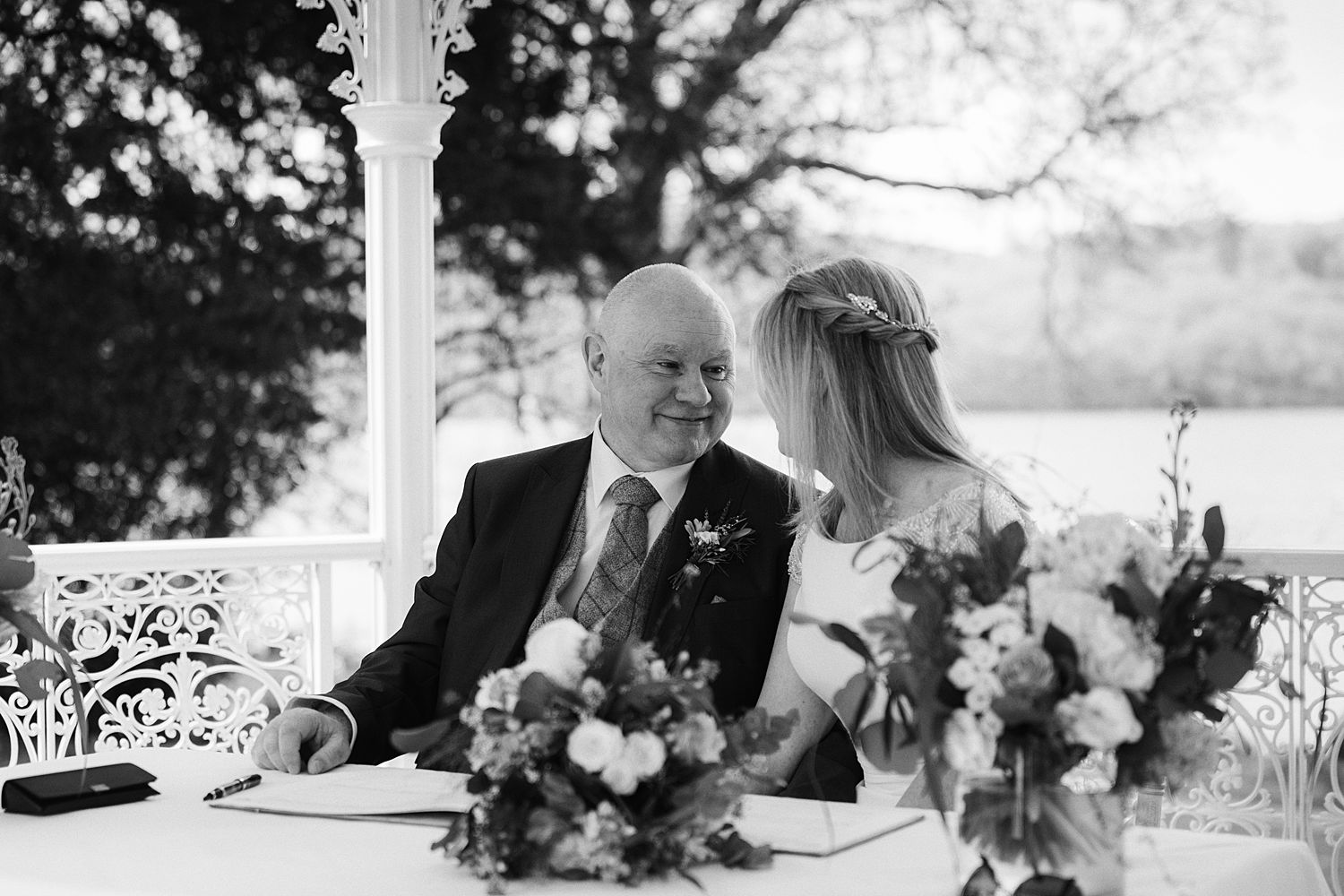 Bride and groom seated to sign register in gazebo overlooking Lake Windermere at Storrs Hall wedding