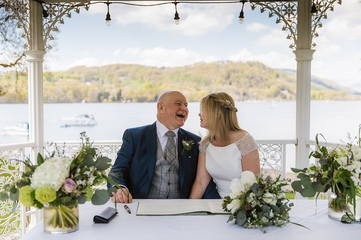 Groom laughing with bride at outdoor wedding venue, Storrs Hall Lake District