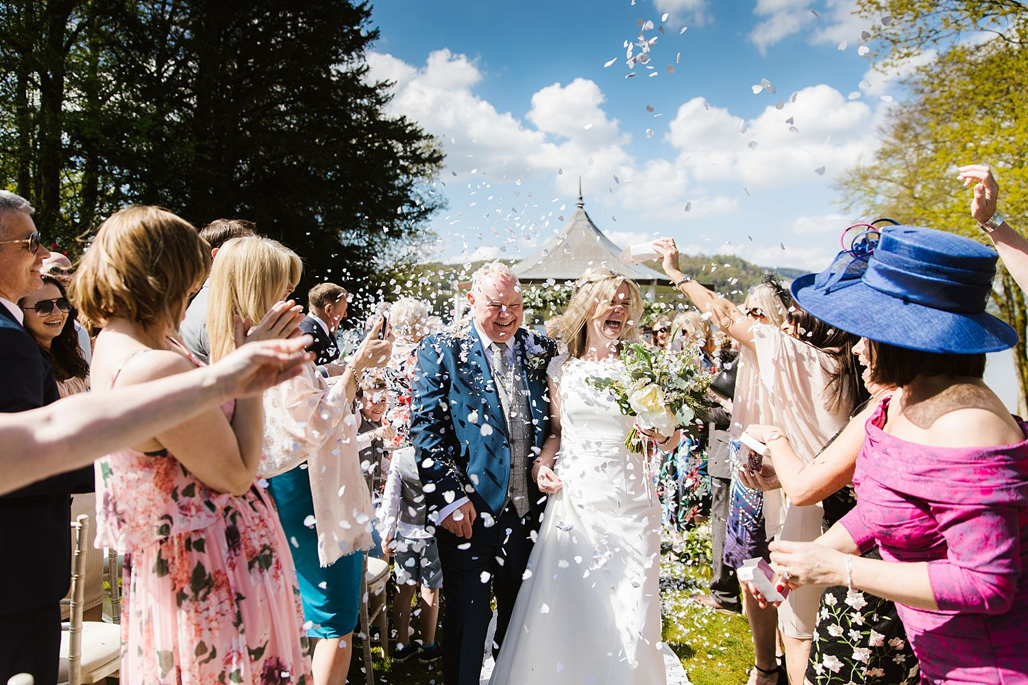 Bride and gorrm, confetti shower at Lake District wedding venue, Storrs Hall