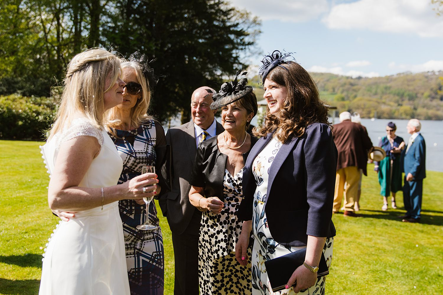 Bride and guests chatting with Lake Windermere in background at Bowness on Windermere wedding venue, Storrs Hall