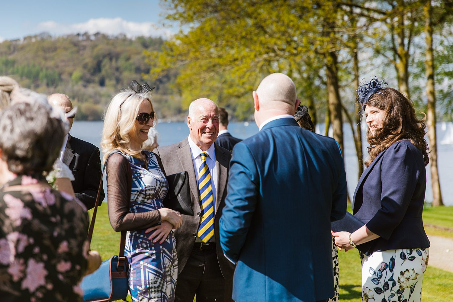 Groom chatting with guests at outdoor wedding reception, at Storrs Hall in Lake District