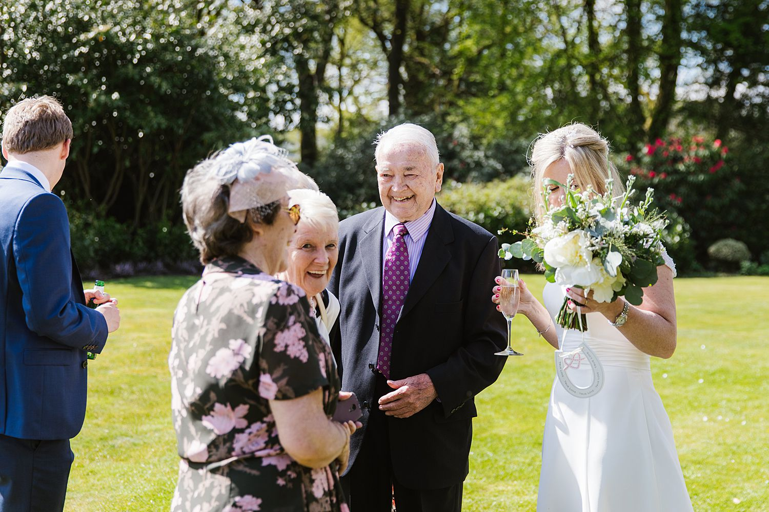 Bride with bouquet chats to guests, bouquet from brackens florist in Windermere, venue Storrs Hall Hotel