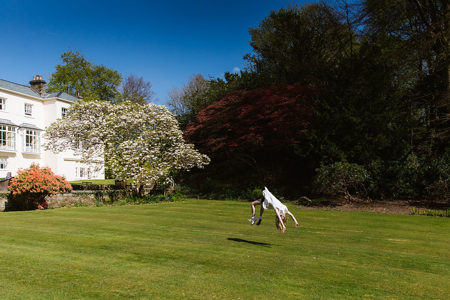 Young guest does hndspring on lawn outside Storrs Hall at Lake District wedding