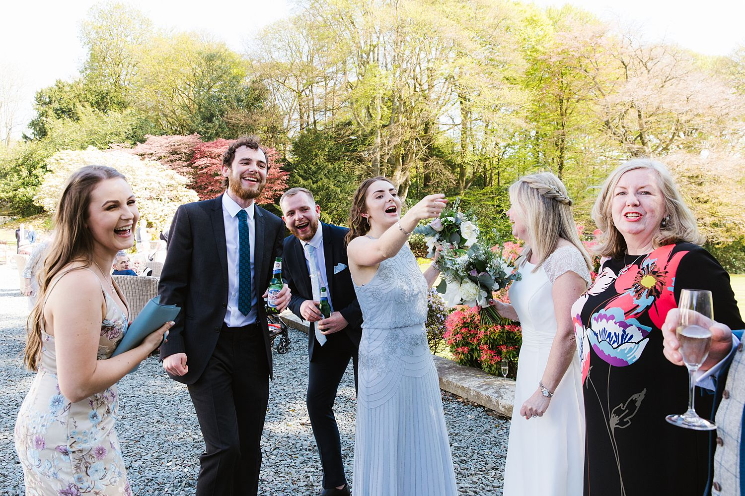 Bride, bridesmaid and giests enjoy champagne at Lake District wedding, Storrs Hall Hotel