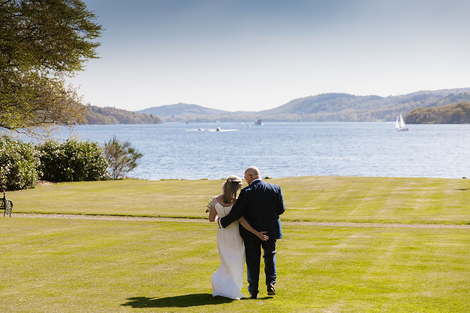 Bride and groom with stunning view of Lake Windermere at Storrs Hall wedding, Cumbria