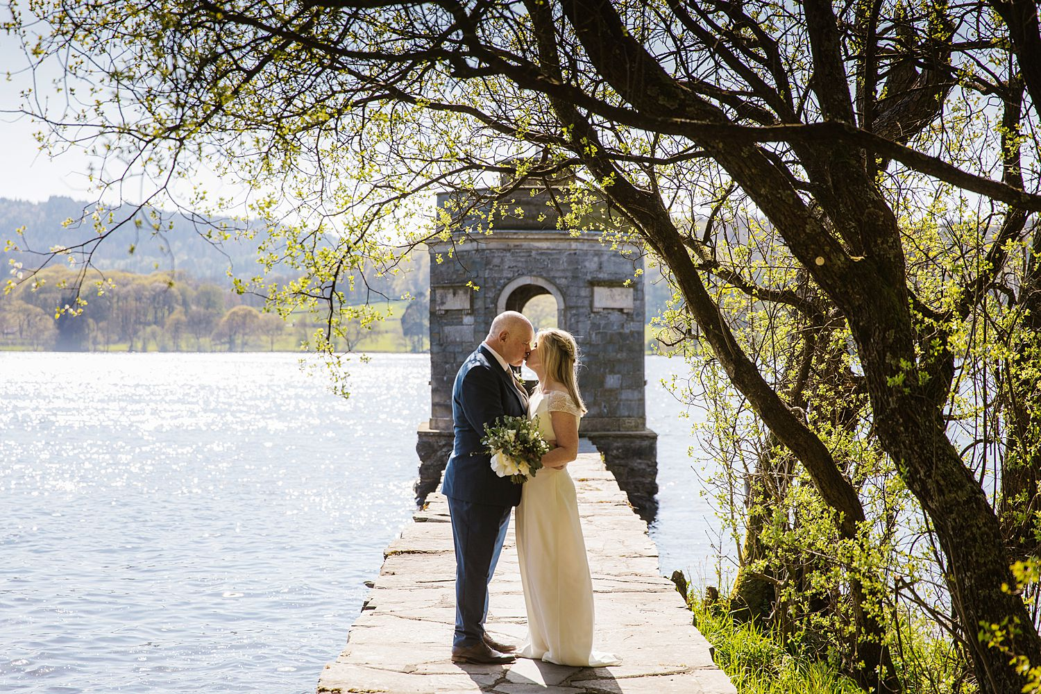 Bride and groom kissing on jetty at Storrs Hall, Bowness on Windermere