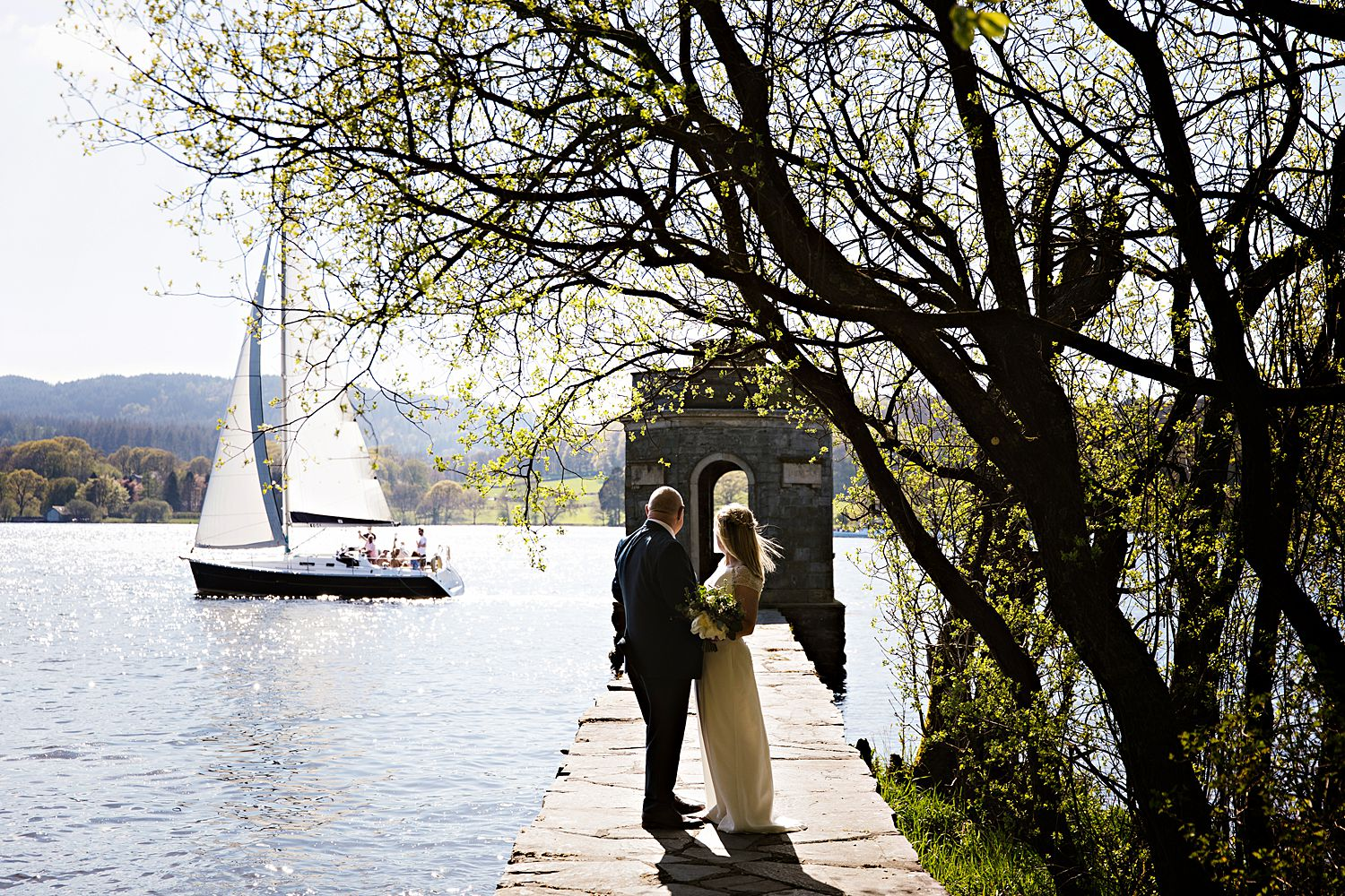 Bride and groom on jetty as yacht passes by on Lake Windermere at Storrs Hall Hotel wedding