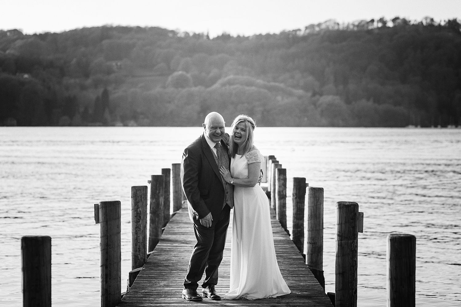 Laughing bride and groom on jetty with Lake Windermere in background, at Storrs Hall Hotel wedding