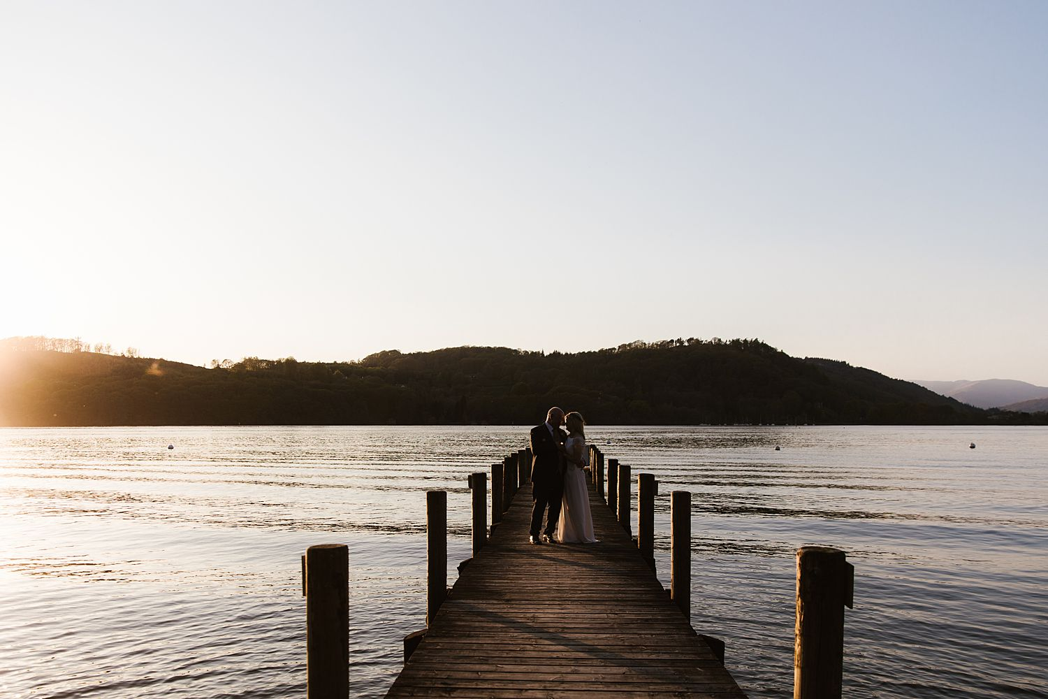 Evening sunset over Lake Windermere, with bride and groom on jetty at Storrs Hall wedding