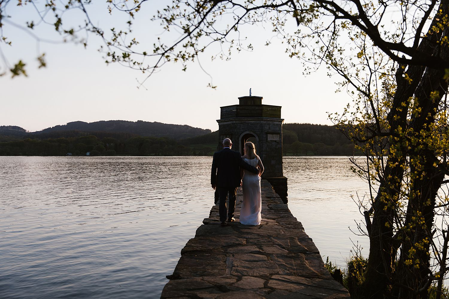 Bride and grrom walk towards follya t end of jetty on Lake Windermere at Storrs Hall Hotel wedding venue