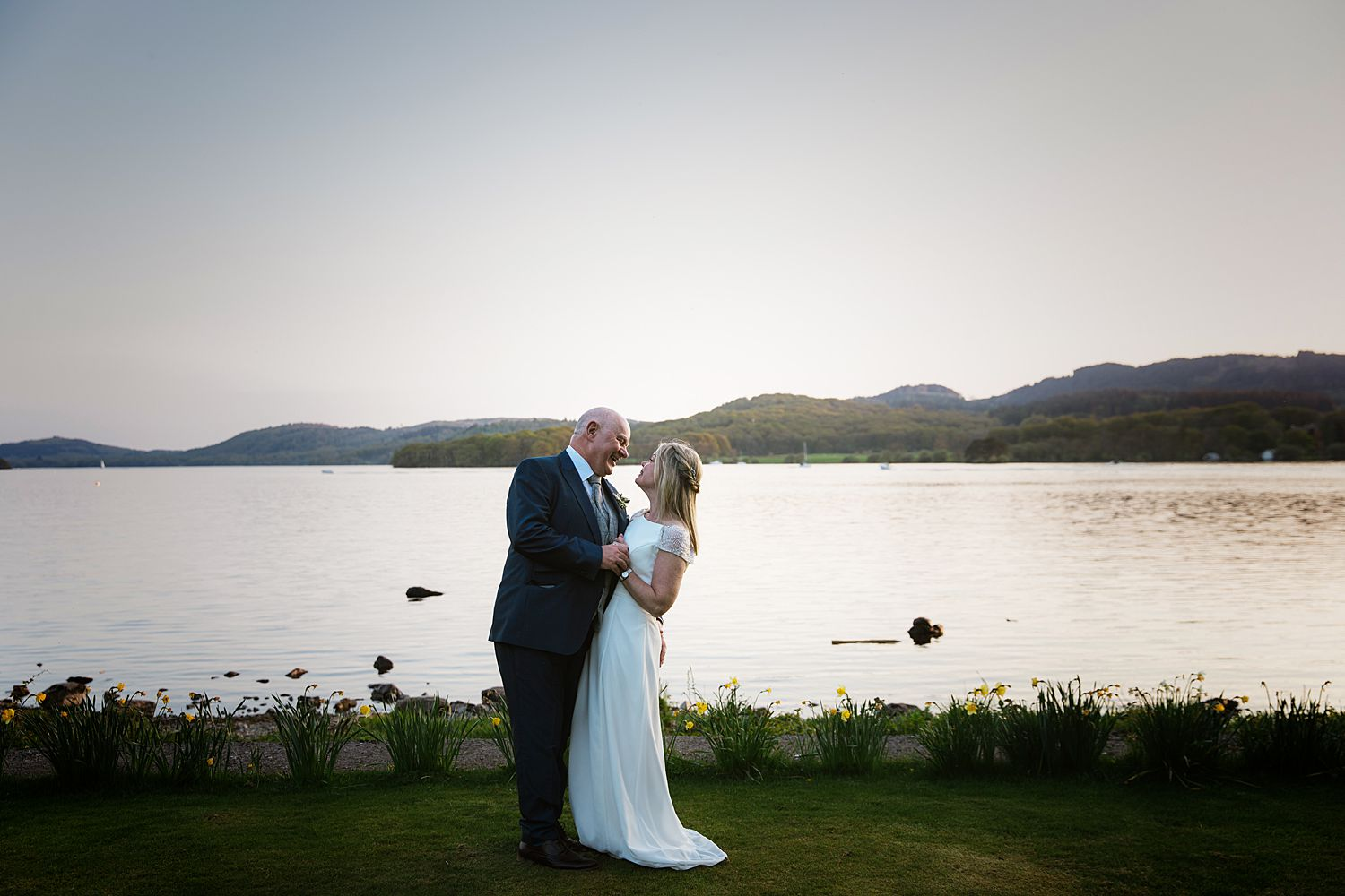 Bride and groom embrace on shore of Lake Windermere at Storrs Hall Hotel