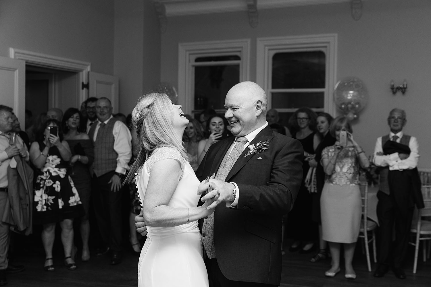 Bride and groom laughing on dancefloor at Storrs Hall wedding, Lake District