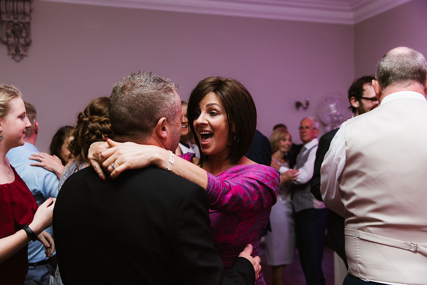 Guests enjoying evening reception on dancefloor at Lake District Storrs Hall Hotel wedding.