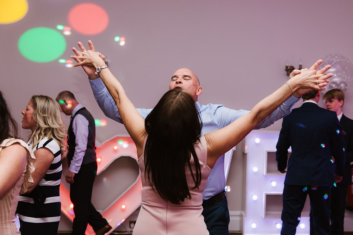 Groom dancing with guest at Storrs Hall Hotel wedding, Bowness on Windermere