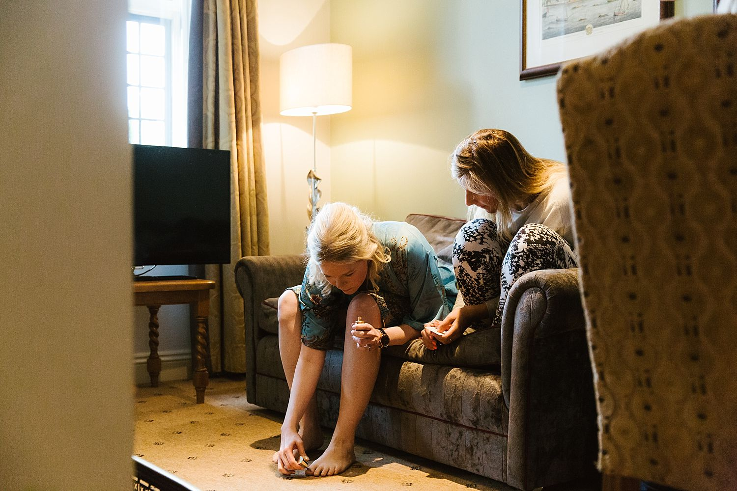 Bridesmaids painting toenails getting ready for Hampton Court House wedding