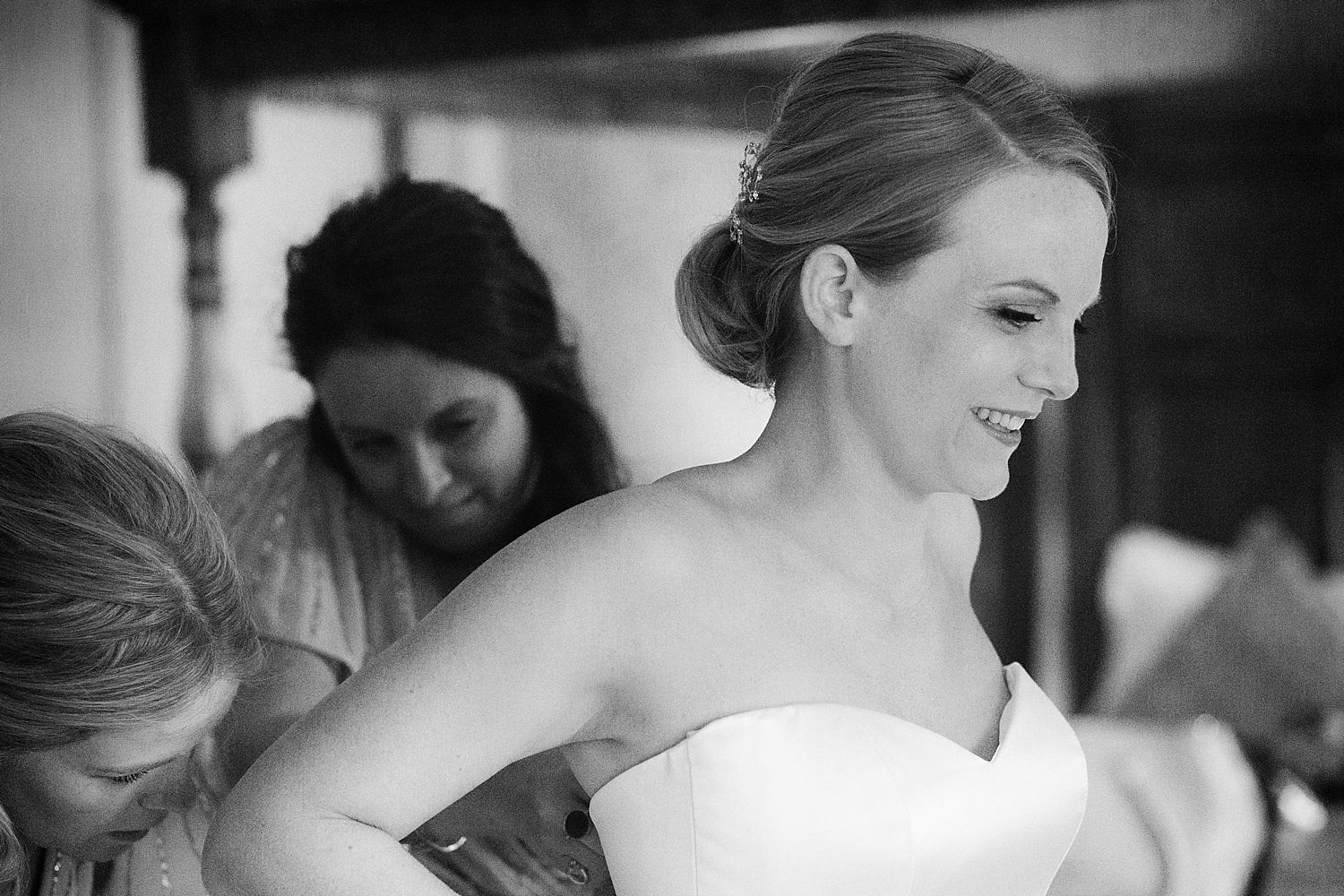 Buttoning up the bride's Stephanie Allin wedding dress at Hampton Court House