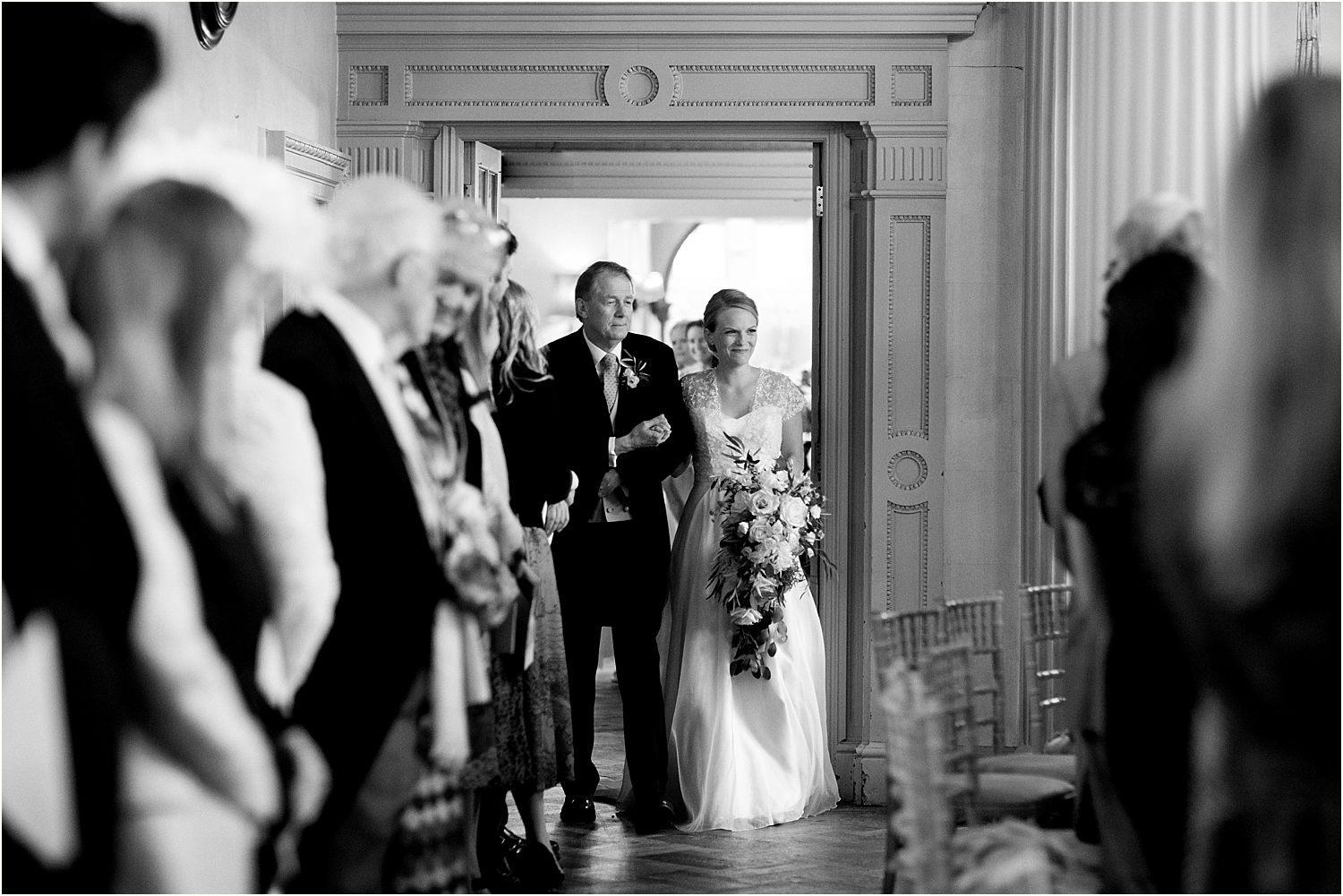Bride in Stephanie Allin dress and her father enter ceremony room for Hampton Court House wedding