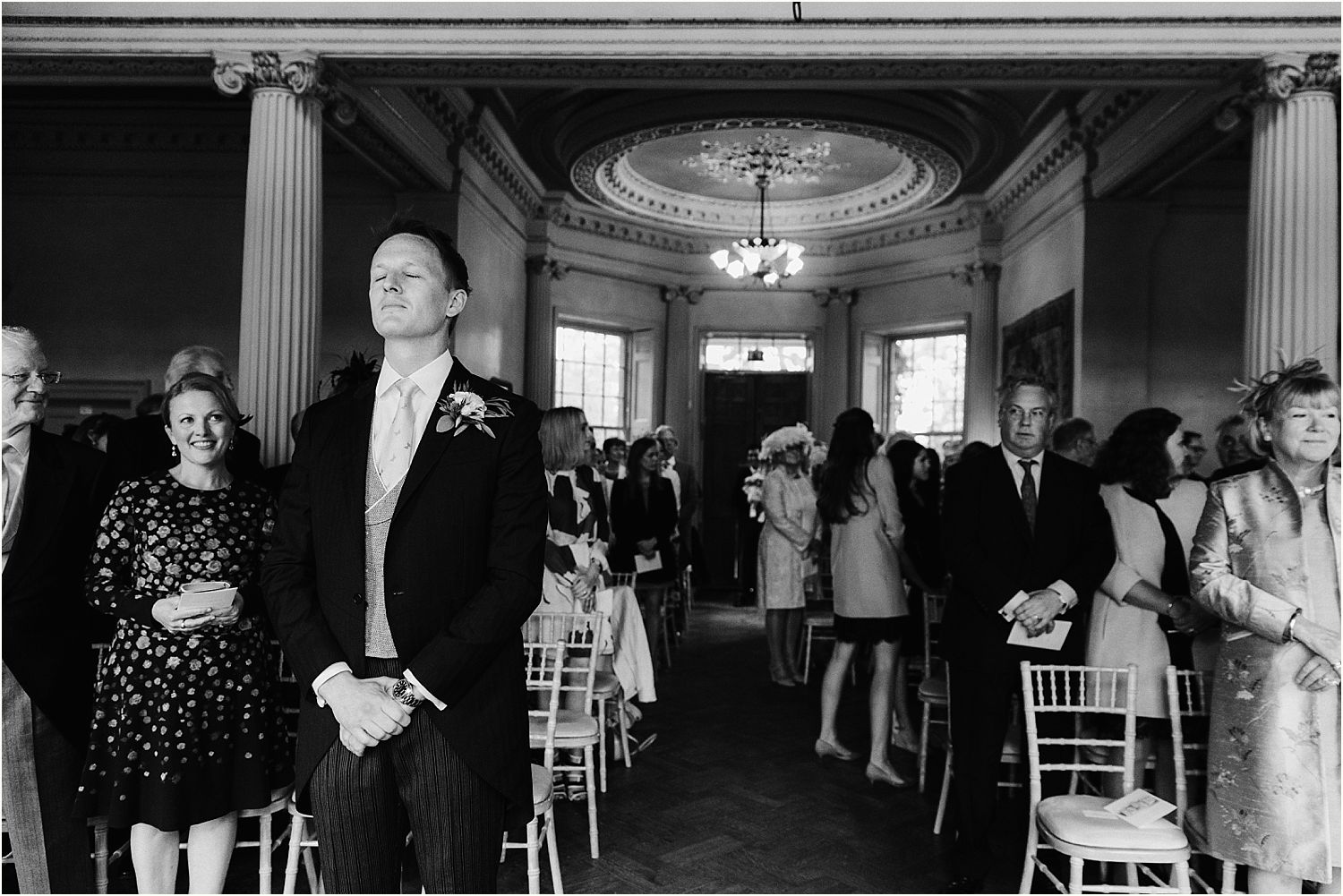 Groom waiting, eyes closed for his bride at Hampton Court House wedding ceremony