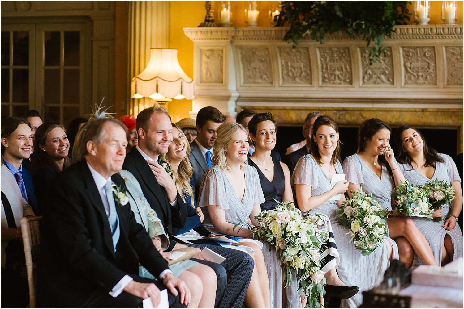 Bridesmaids and guests enjoy reading at wedding ceremony at Hampton Court House