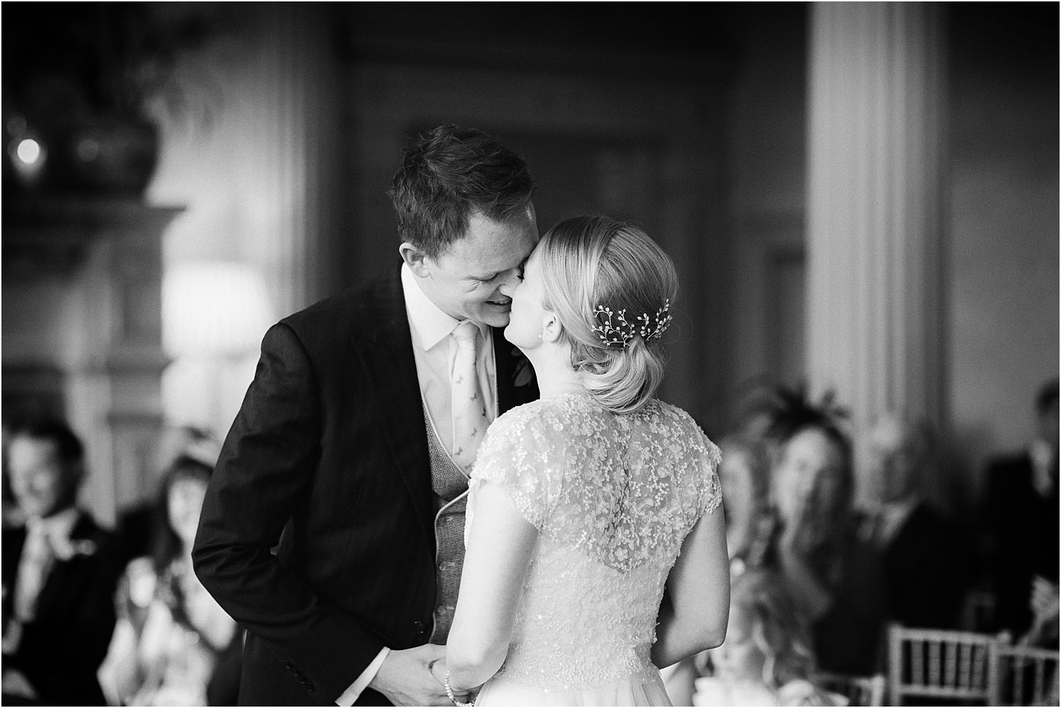 Bride and groom exchange a kiss at their Hampton Court wedding Surrey, hair and make up by Lillie Lindh and Kari Rodnes