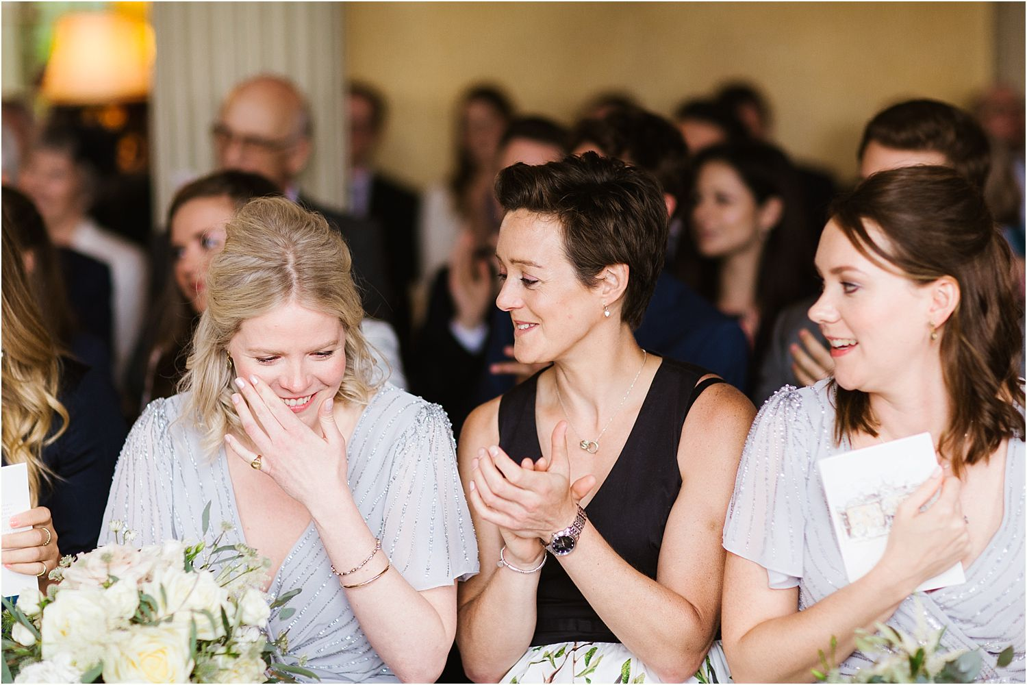 Bridesmaids and guests laughing during ceremony at Hampton Court House wedding