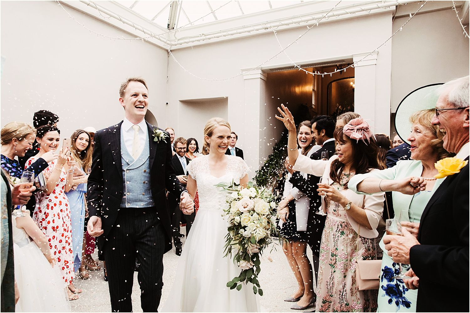 Bride and grrom in confetti showwr at Hampton Court wedding, bride's bouquet by Gabi Burton, The Fine Flowers Company