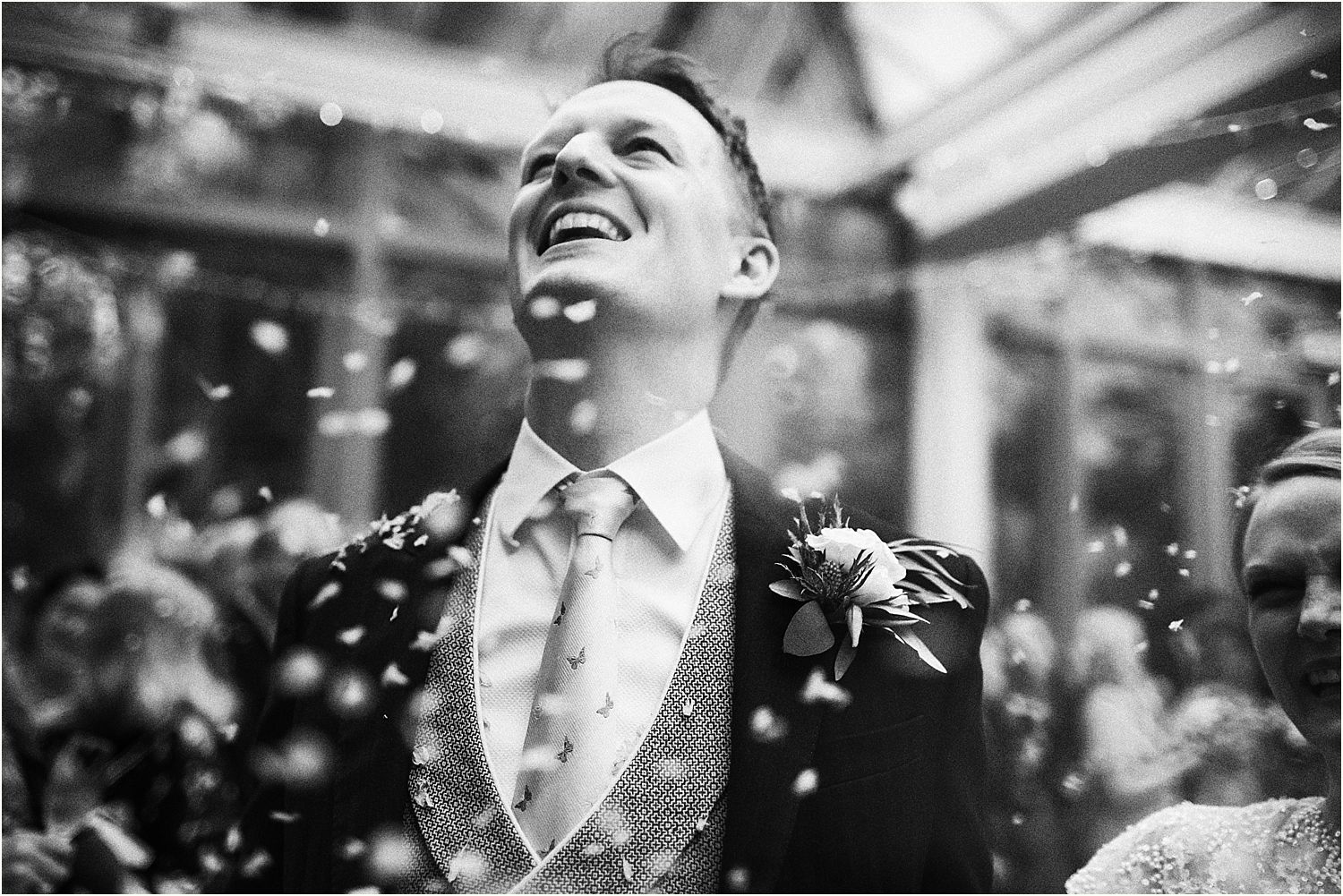 Groom laughing at confetti around him at Surrey wedding venue Hamtpon Court House