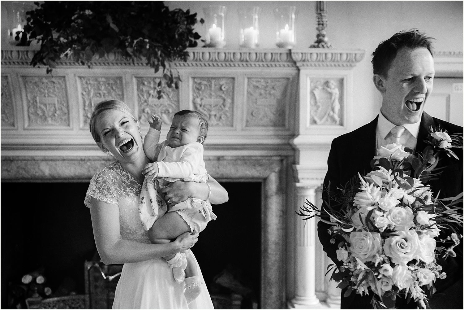Bride holding crying baby, groom holding bouquet by The Fine Flowers Company at Surrey wedding