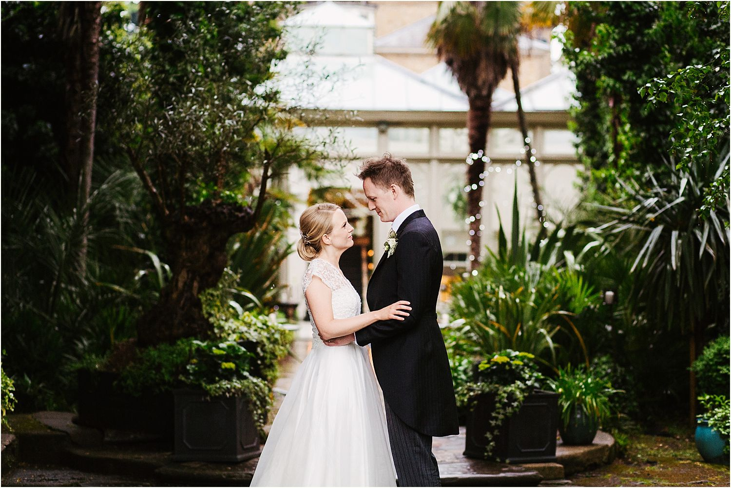 Bride and groom together in gardens at Hampton Court House wedding venue, Surrey