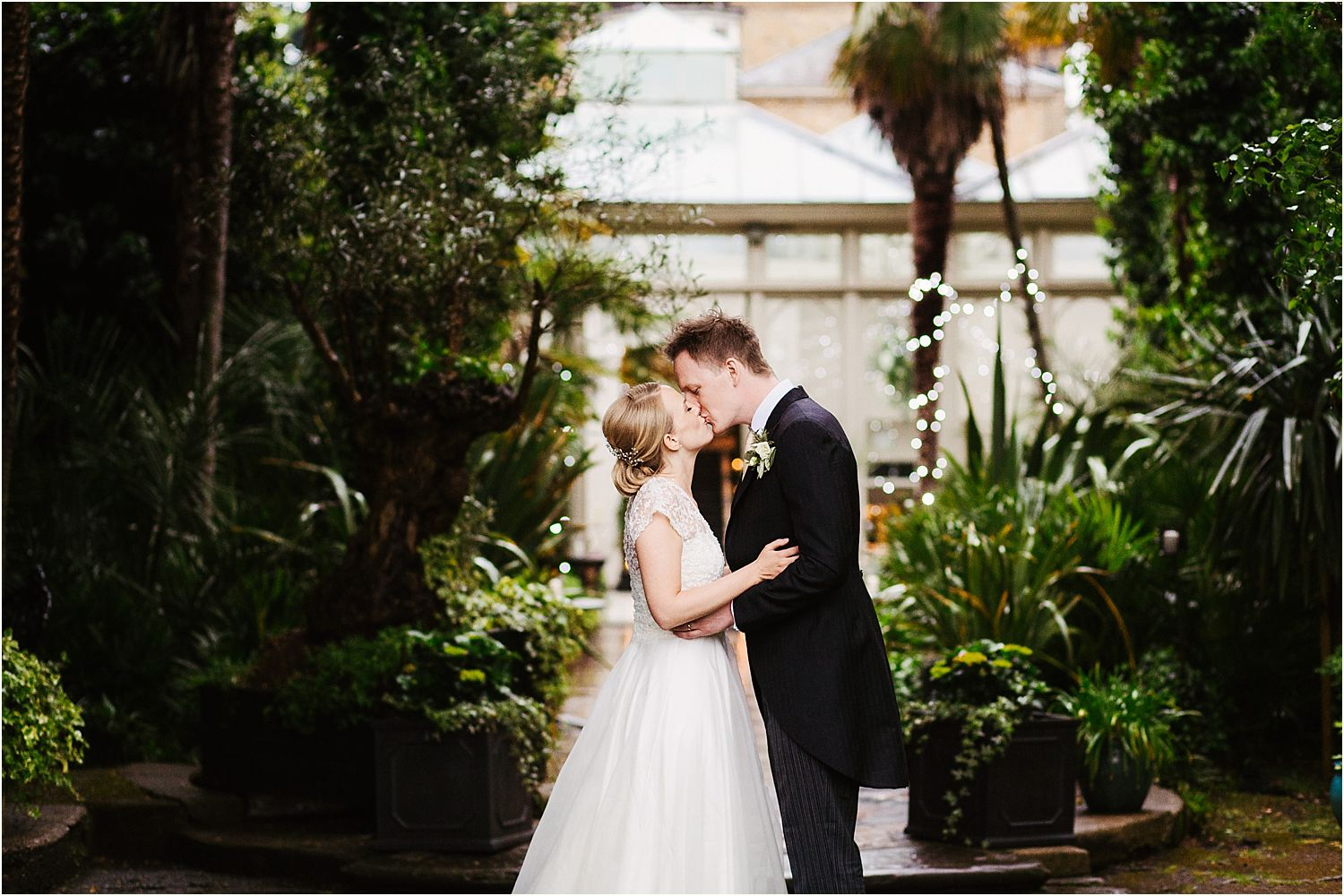 Bride and groom share a kiss in the gardens at Hampton Court House