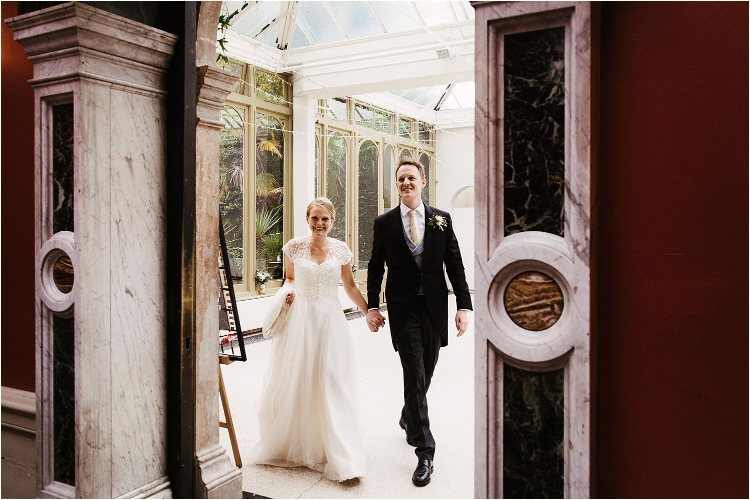 Bride in Stephanie Allin dress and groom enter reception at Hampton Court House
