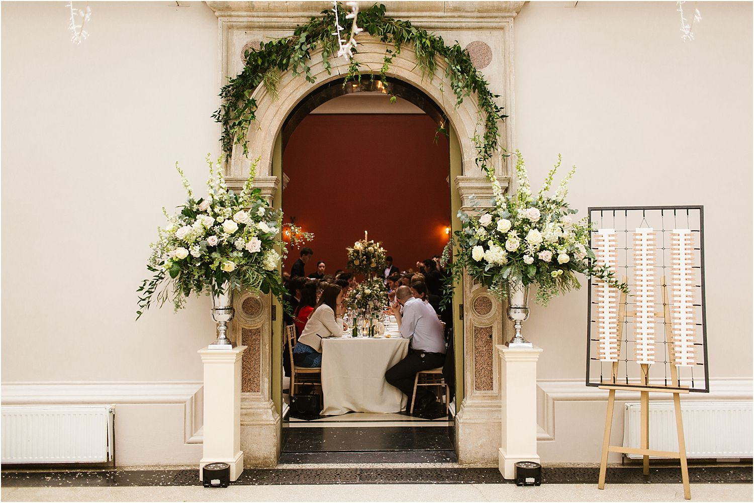 Floral art by The Fine Flowers Company decorates arched doorway at Hampton Court House wedding