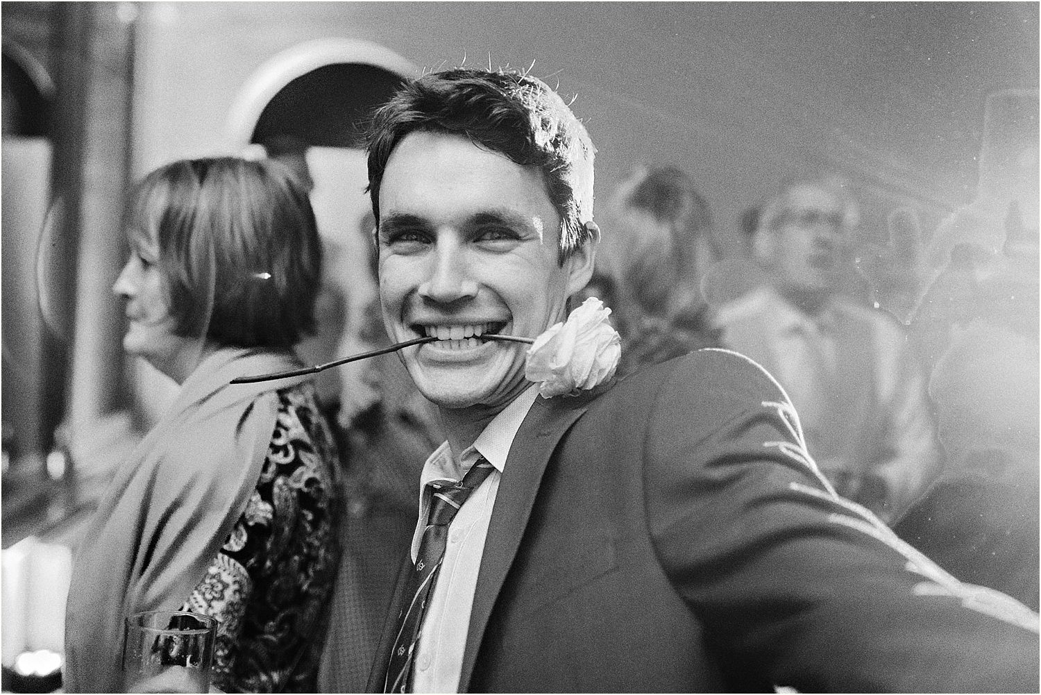 Guest with rose in his teeth at Hampton Court House wedding