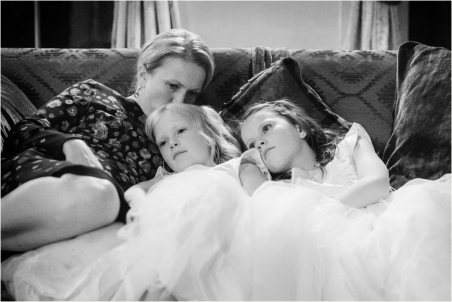Tired little bridesmaids snuggled on sofa at Hampton Court House wedding