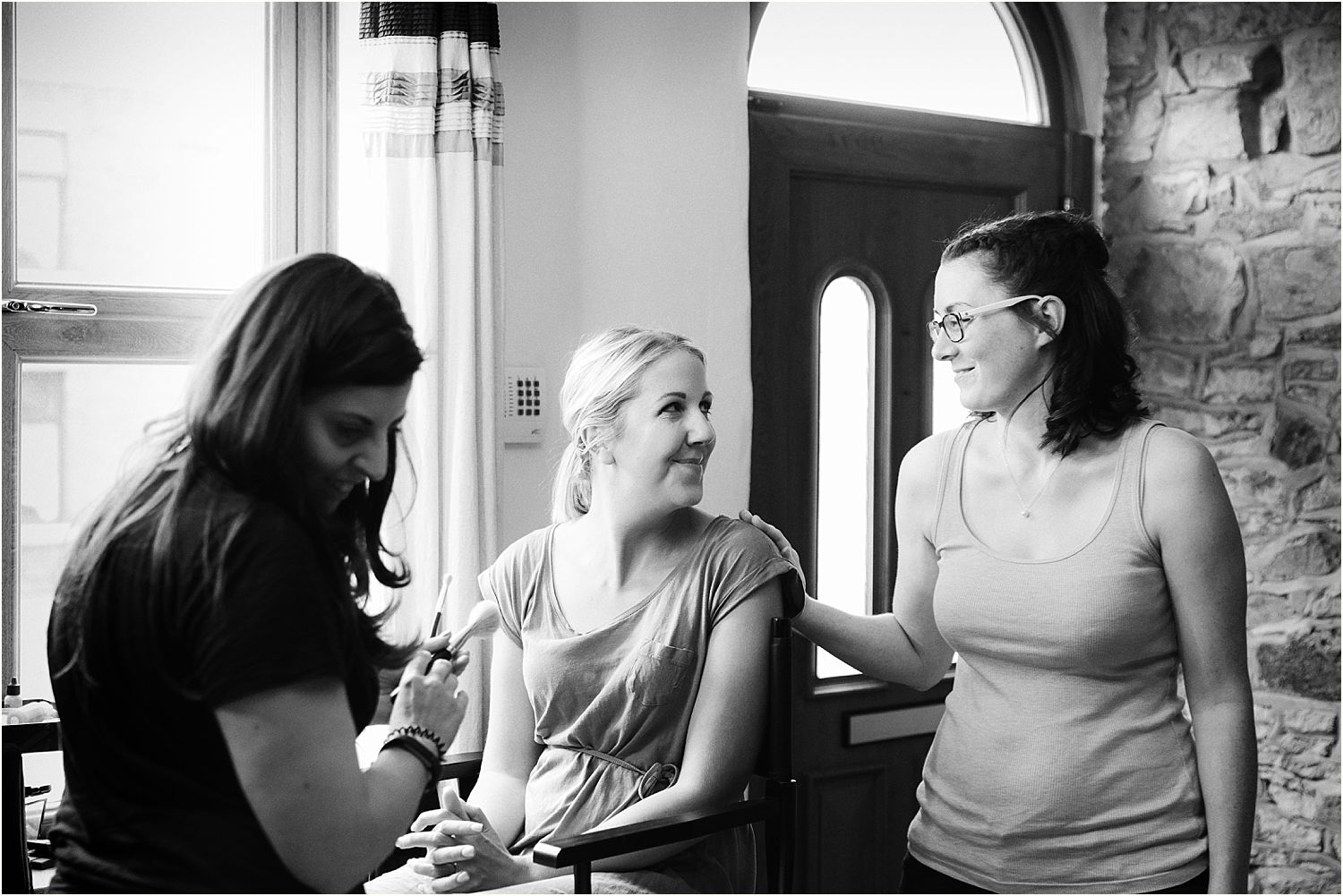 Bridal prpearations, bride in make up chair chatting with her friend prior to Lancashire farm wedding