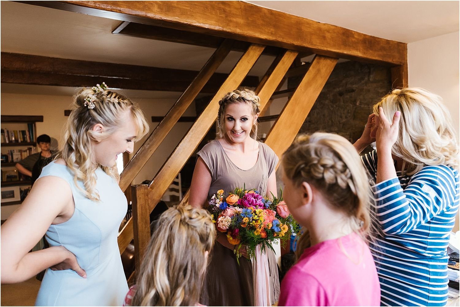 Bride, bridesmaids and children chatting whilst getting ready for Lancashire farm wedding