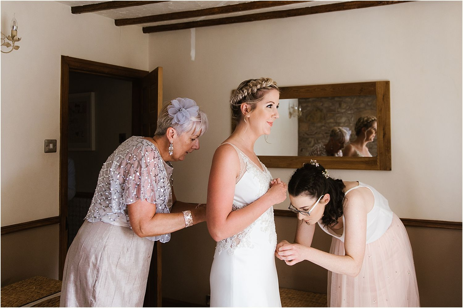 Brides mother and bridesmaid buttongin up dress and attending to bride. Wedding dress by Maggie Sottero from the Bridal Lounge in Accrington