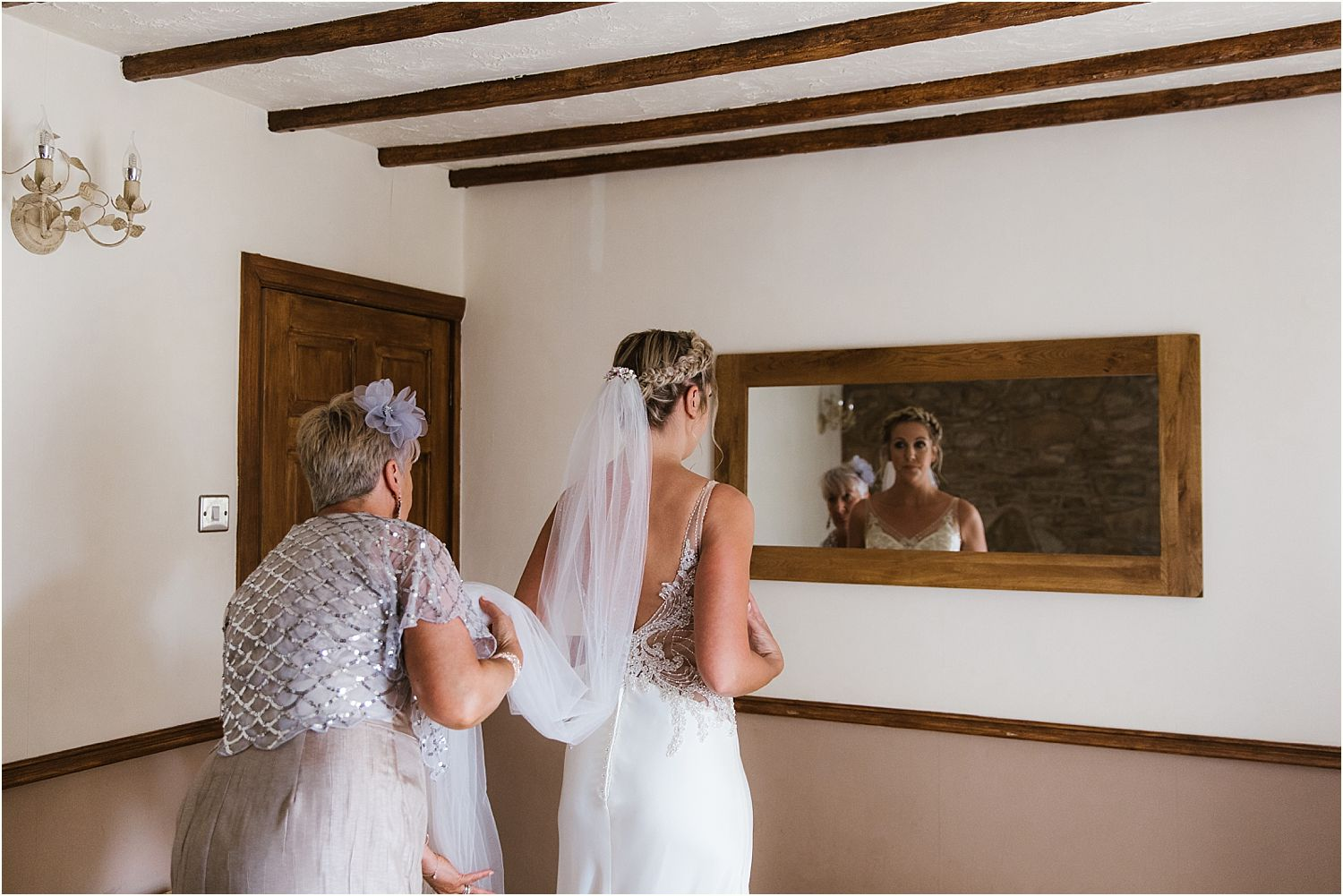 Positioning the bride's veil prior to Lancashire farm wedding. Bride's accessories by The Bridal Lounge of Accrington