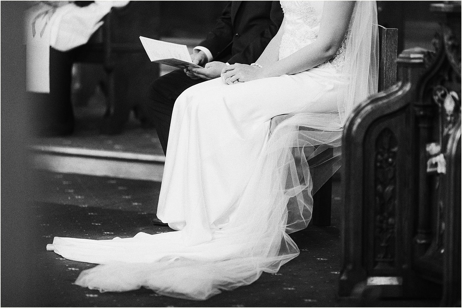 cropped image of bride and groom holding order of service for rural Lancashire wedding