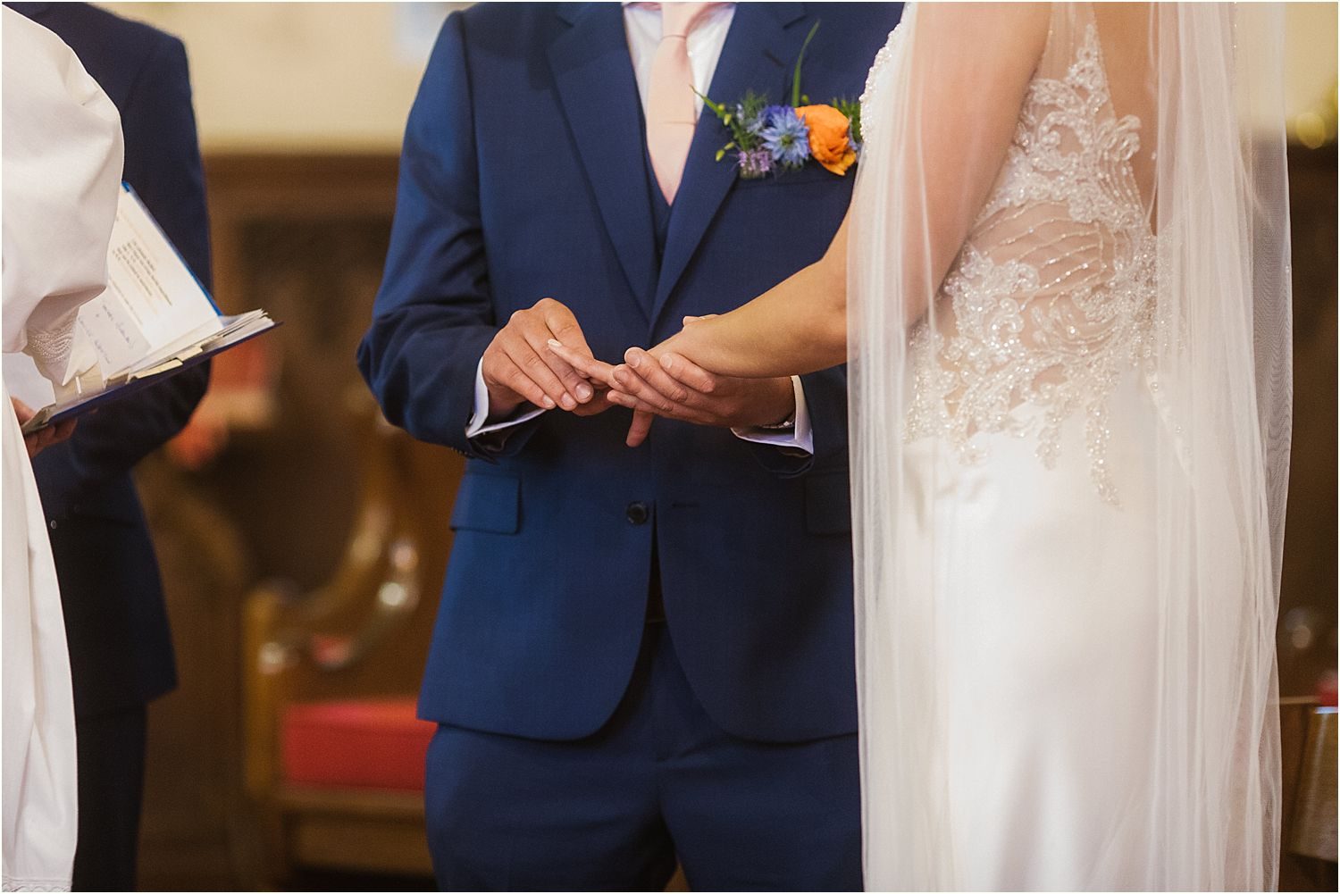 groom places ring on brides finger at wedding in Lancashire
