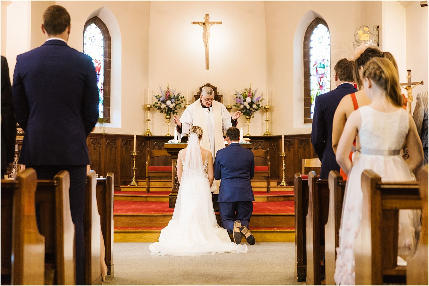 Bride and groom kneeling at the altar at Lancashire wedding