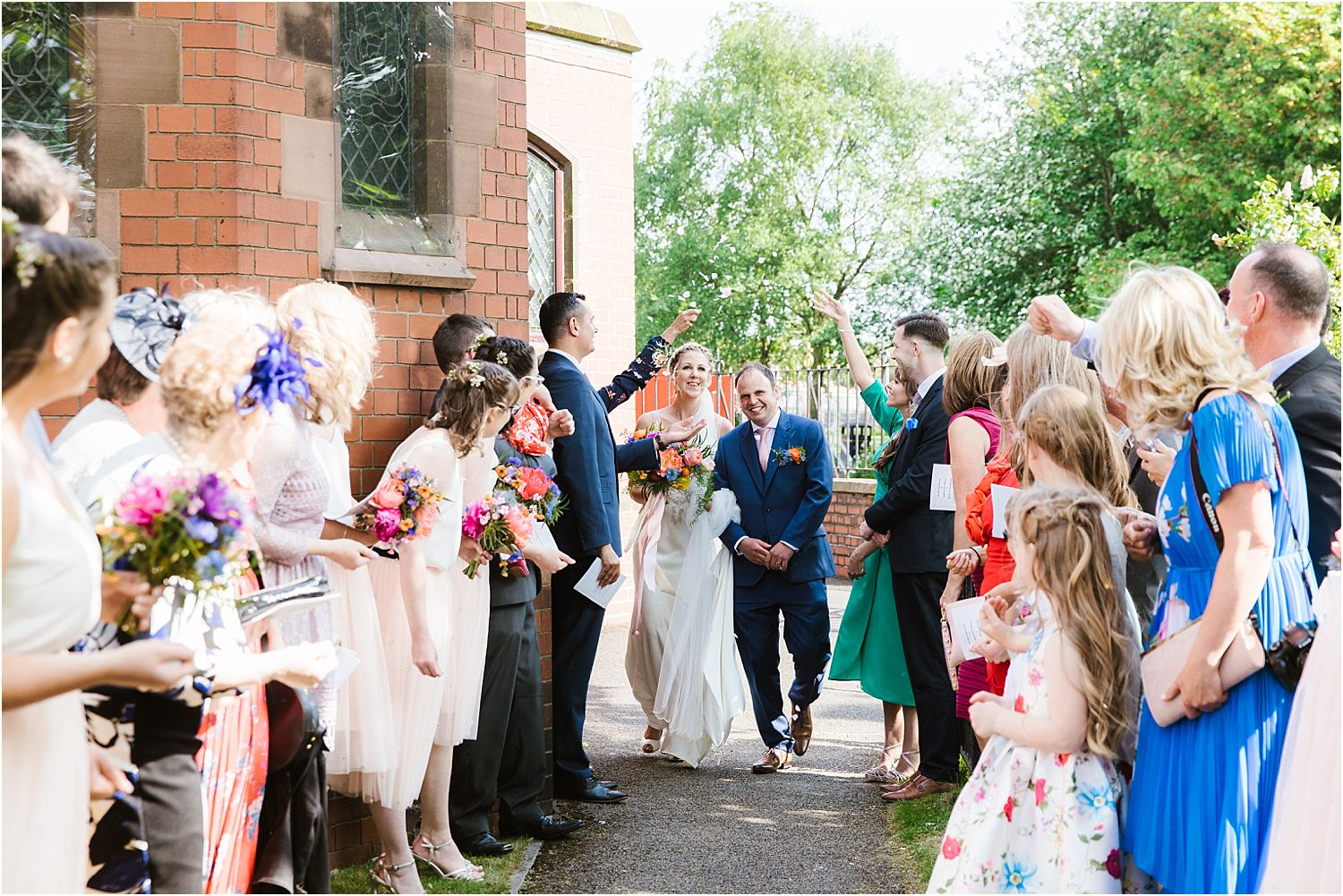 Bride and groom walking through avenue of guests prior to confetti being thrown at Lancashire wedding