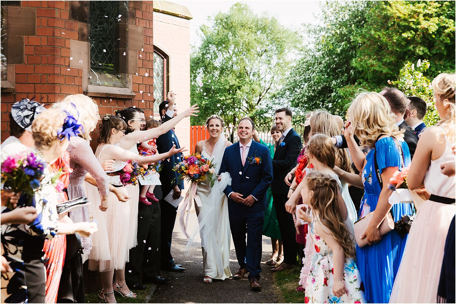 Bride and groom in confetti line up at Lancashire wedding
