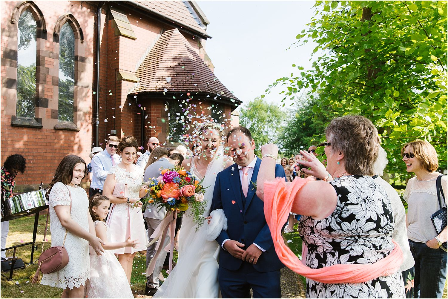 Bride and groom in confetti shower at Lancashire wedding