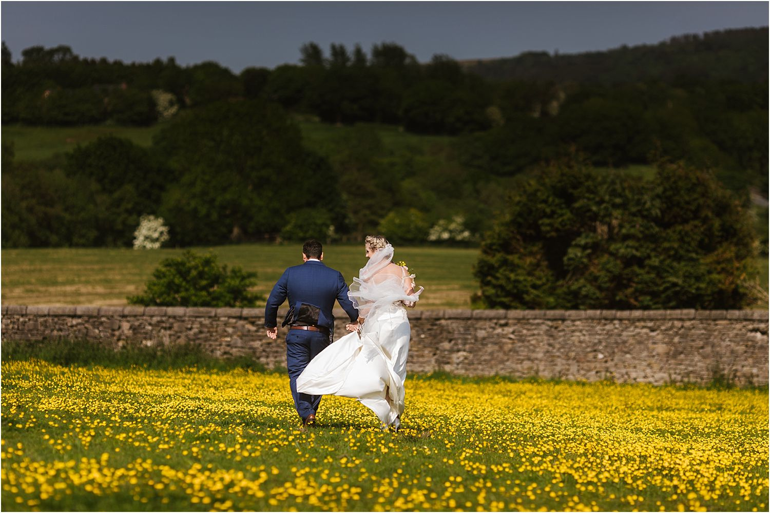 Bride and groom running across buttercup meadow at rural Lancashire wedding