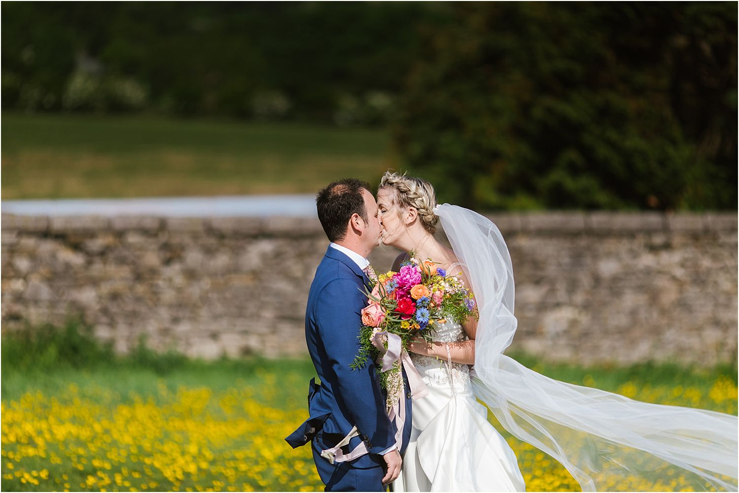 Bride and groom kissing in buttercup meadow at Lancashire wedding. Flowers by Felicity Farm Flowers
