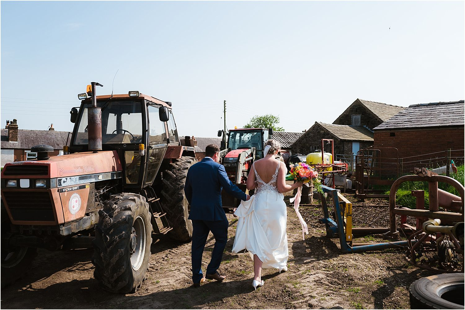 Bride and grrom walking through working farmyard surrounded by tractors and machinery at Lancashire wedding