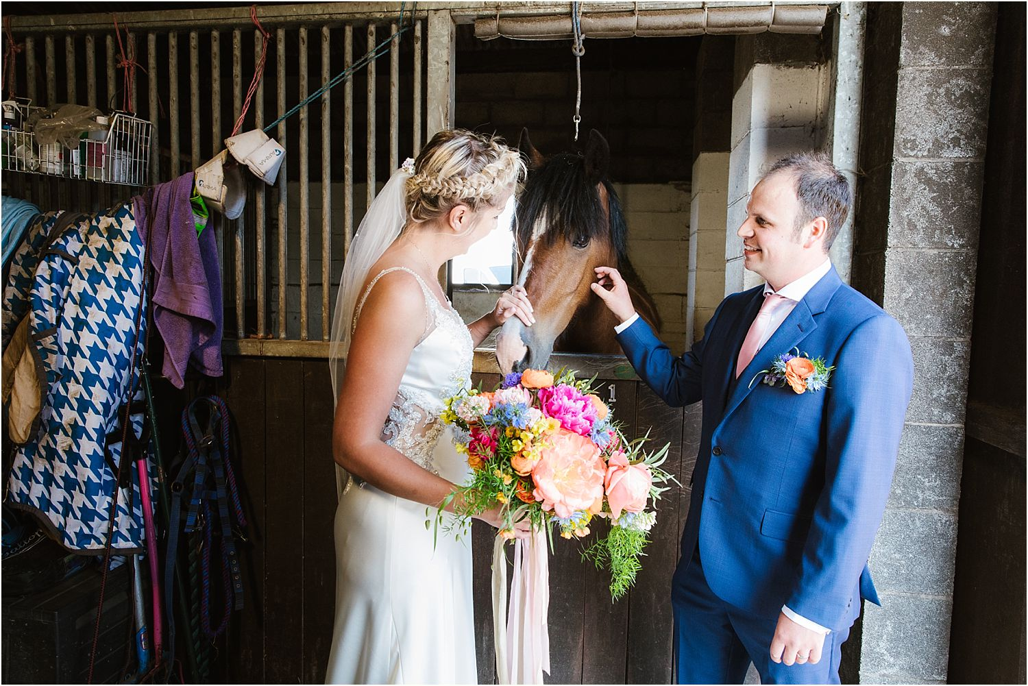 Bride and bridegroom with horse in stable at rural Lancashire wedding