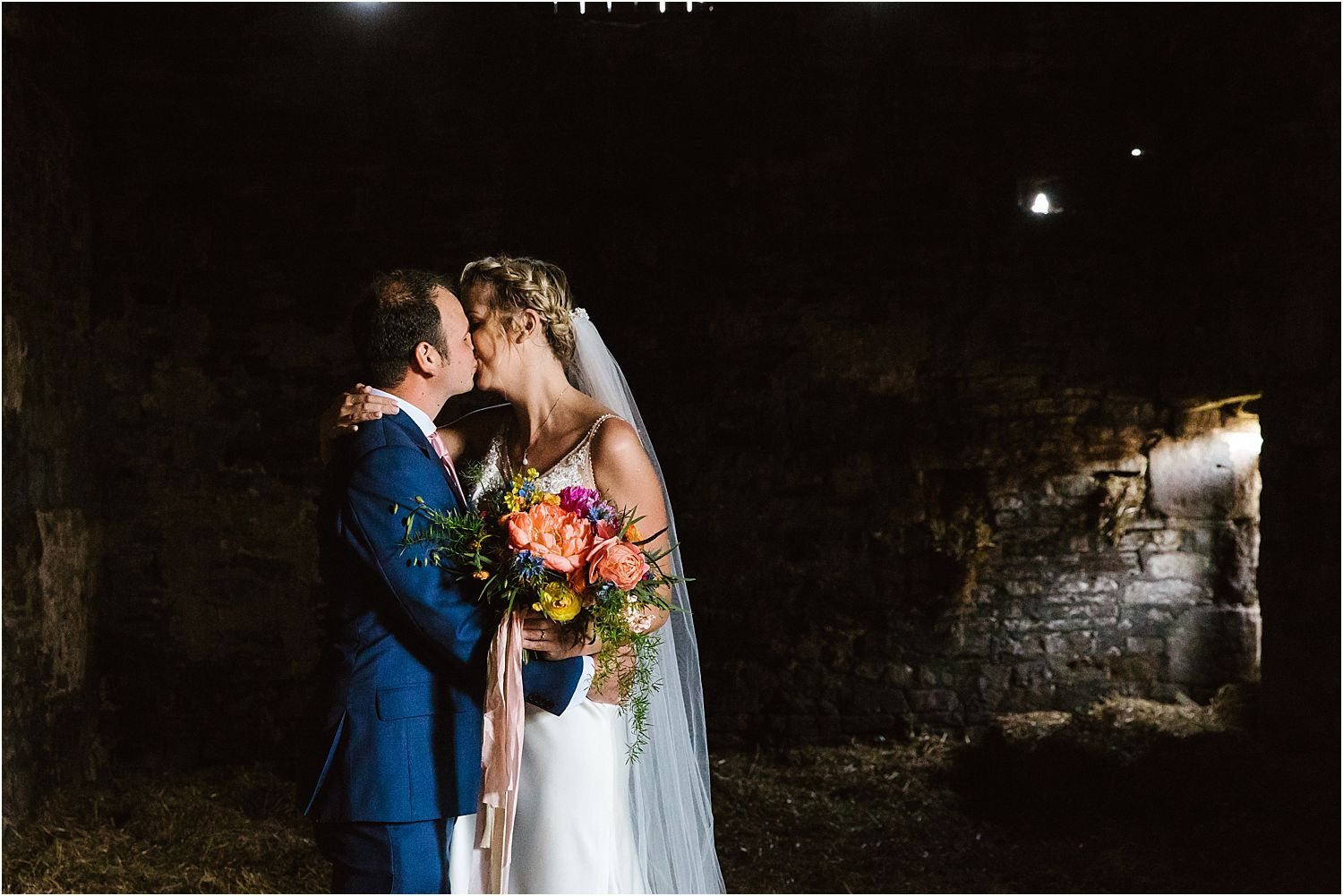 Bride and groom kissing in stable at Lancashire farm wedding